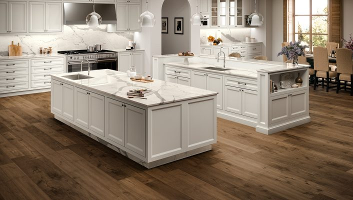 White porcelain kitchen worktops in a marble-effect installed on top of white kitchen units, sitting on a wooden floor